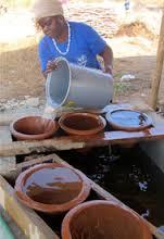 Γυναίκα γεμίζει νερό κεραμικό φίλτρο Αφρική